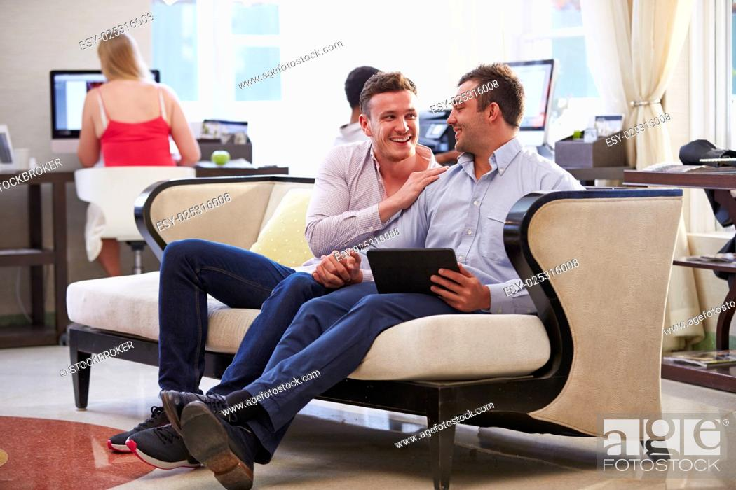 Stock Photo: Male Couple Sitting In Hotel Lobby Looking At Digital Tablet.
