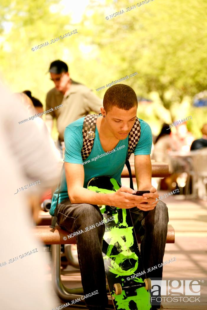 Stock Photo: A young man texting on a college campus.