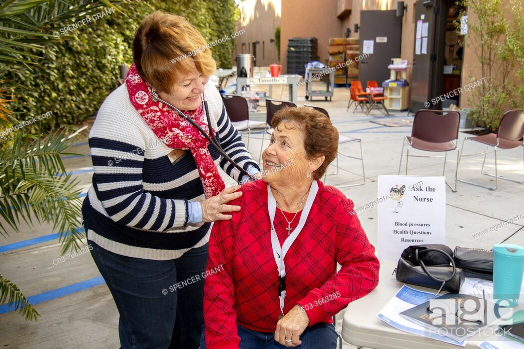 Stock Photo: Using a stethoscope, a volunteer nurse give a fellow volunteer a free medical checkup at the charity food pantry of a Southern California Catholic church.