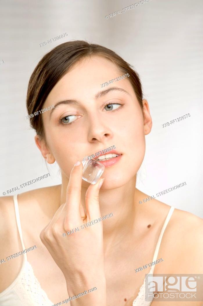 Stock Photo: young woman touching face with ice cube.