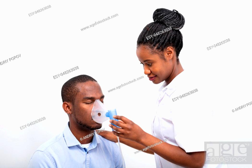 Stock Photo: Young Female Placing Inhaler Mask On Man Mouth Over White Background.