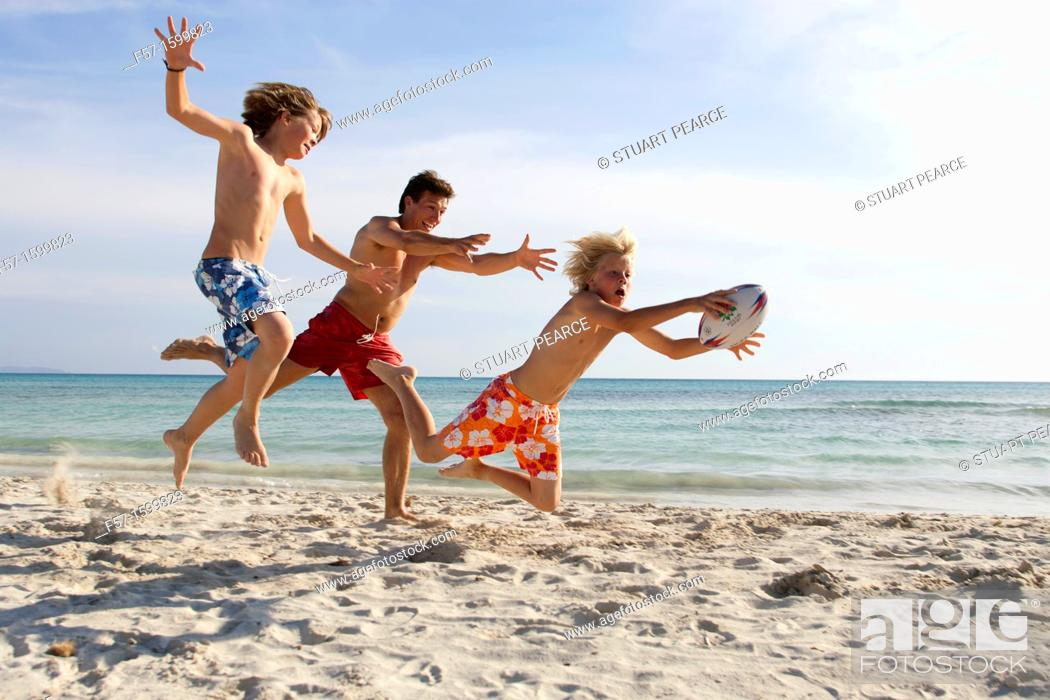 Stock Photo: Father and sons playing ball on the beach.