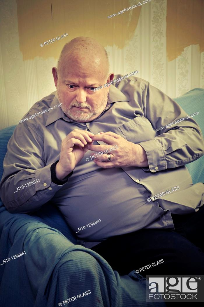 Stock Photo: Balding, middle-age man sitting on a sofa.