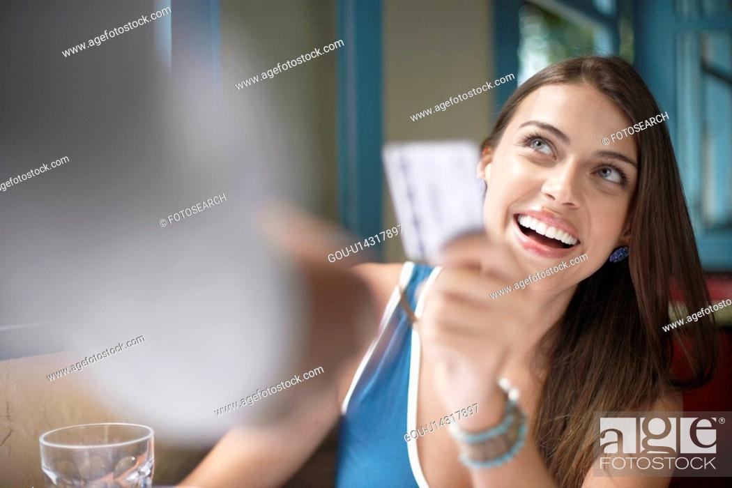 Stock Photo: Woman giving credit card to waiter.