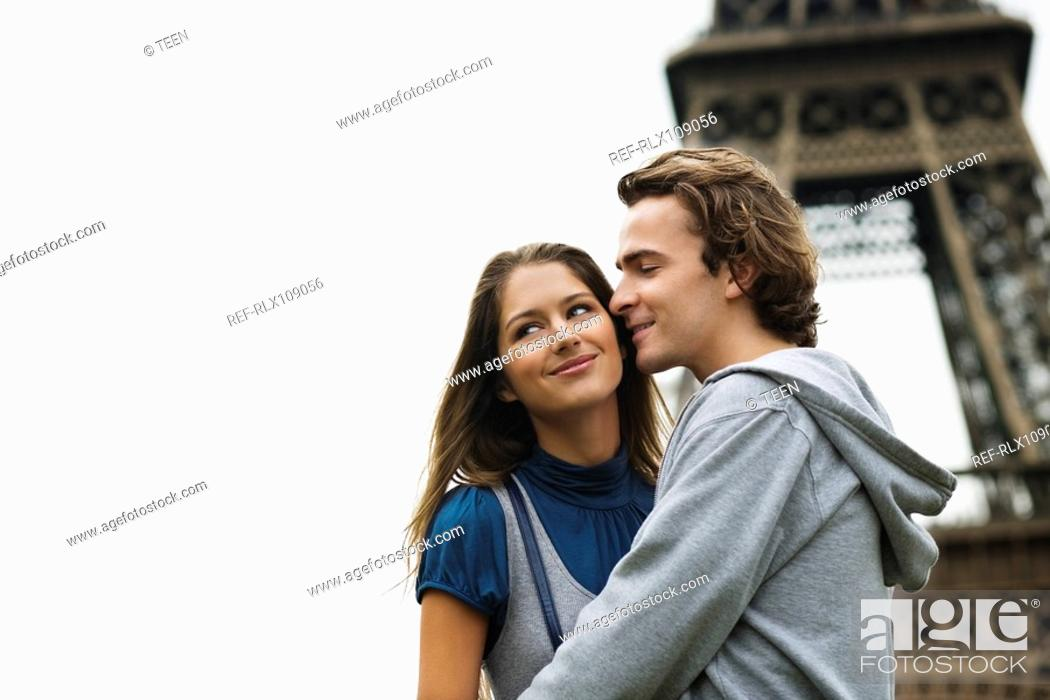 Stock Photo: Young couple kissing with Eiffel tower in background, Paris, France.