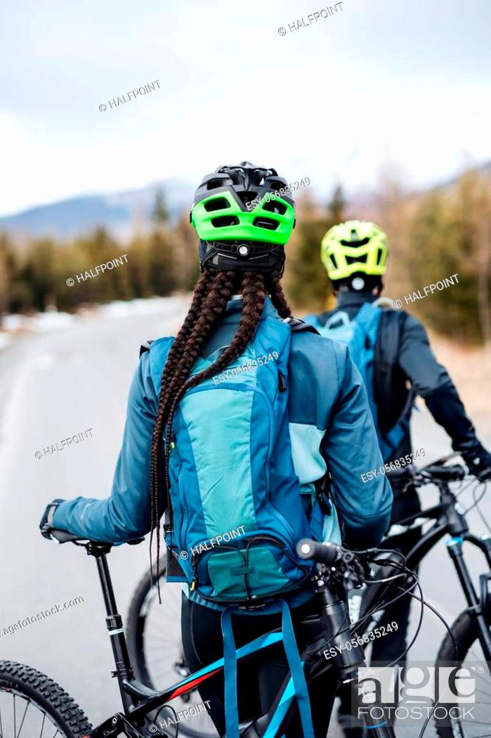 Imagen: A rear view of two mountain bikers on road outdoors in winter.