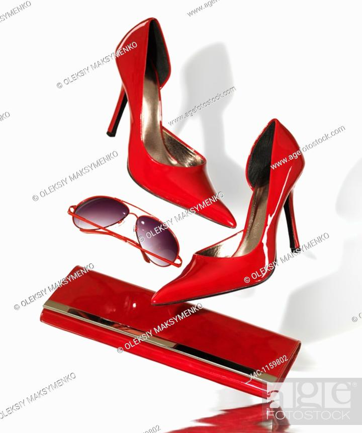 Stock Photo: Stylish red high heel stiletto shoes sunglasses and a clutch hand bag falling on metal surface isolated on white background.