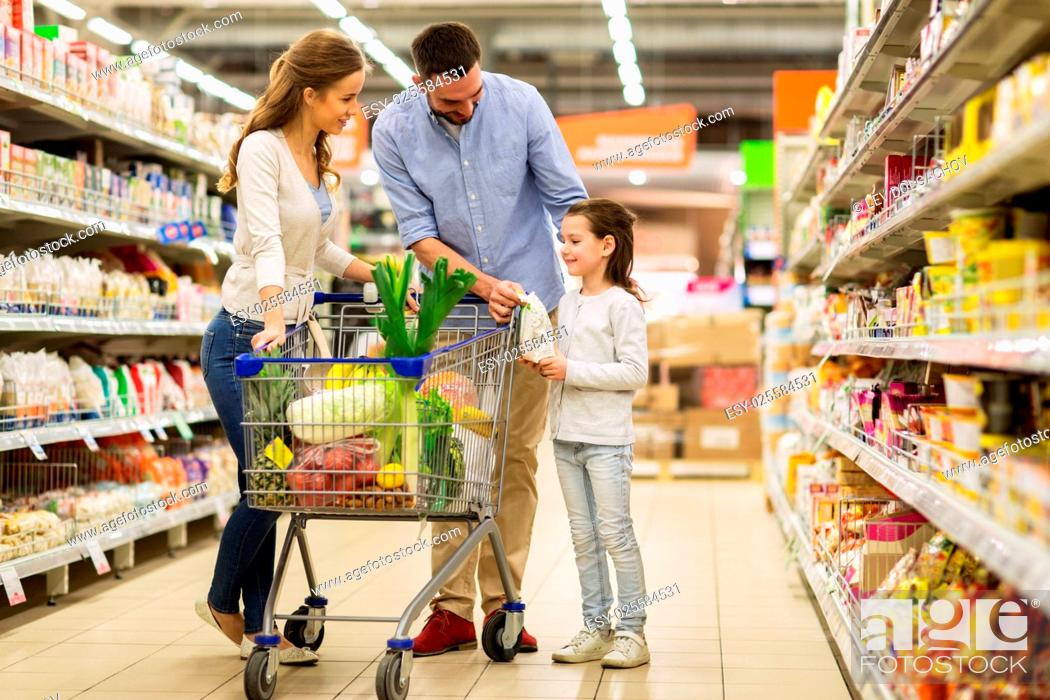 Stock Photo: sale, consumerism and people concept - happy family with child and shopping cart buying food at grocery storeor supermarket.