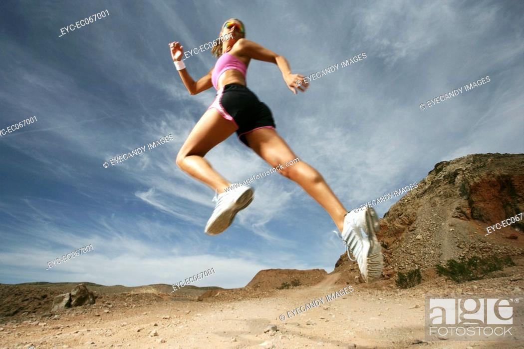 Stock Photo: Caucasian woman jumping up in air during exercise.