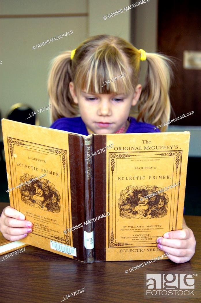 Stock Photo: Child reading the Origianl McGuffey Ecletic Primer.
