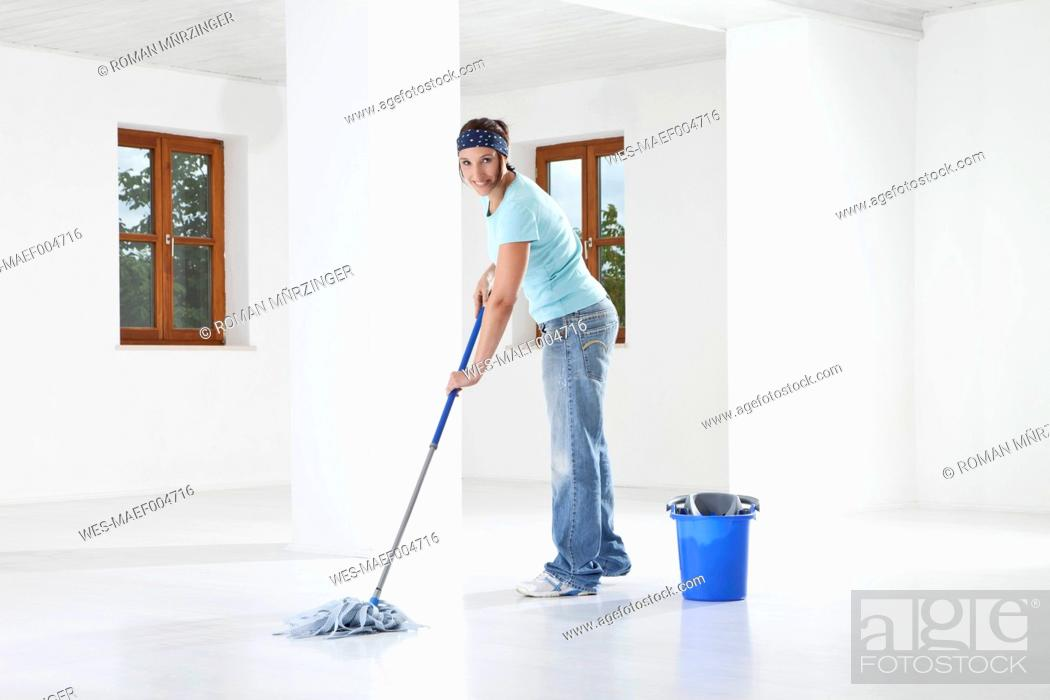 Stock Photo: Germany, Bavaria, Young woman mopping floor, smiling, portrait.