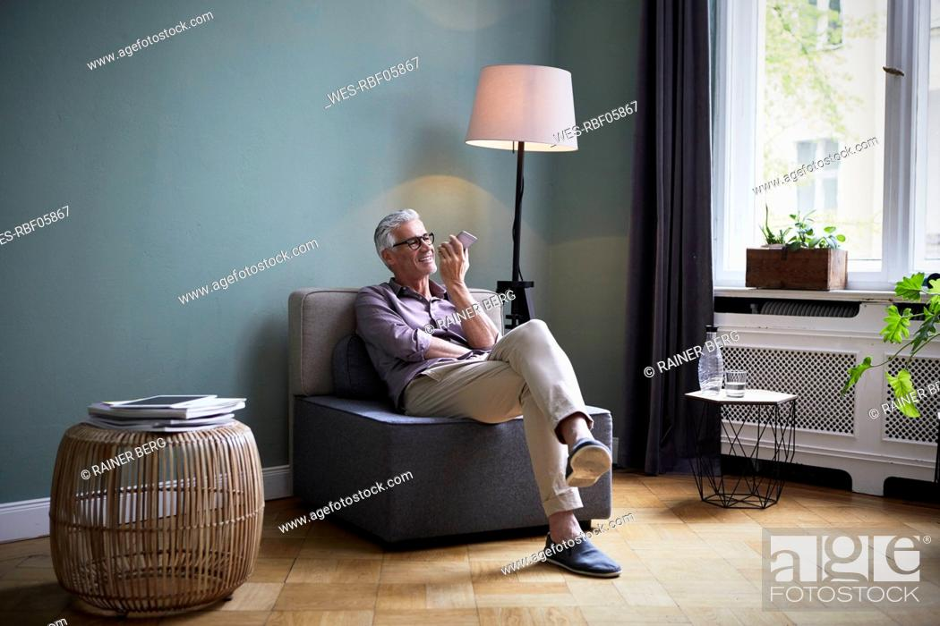 Stock Photo: Mature man using cell phone at home.