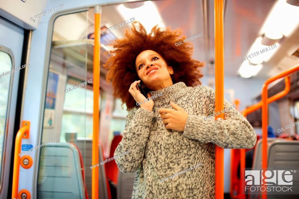 Stock Photo: Woman using mobile phone on train, London.