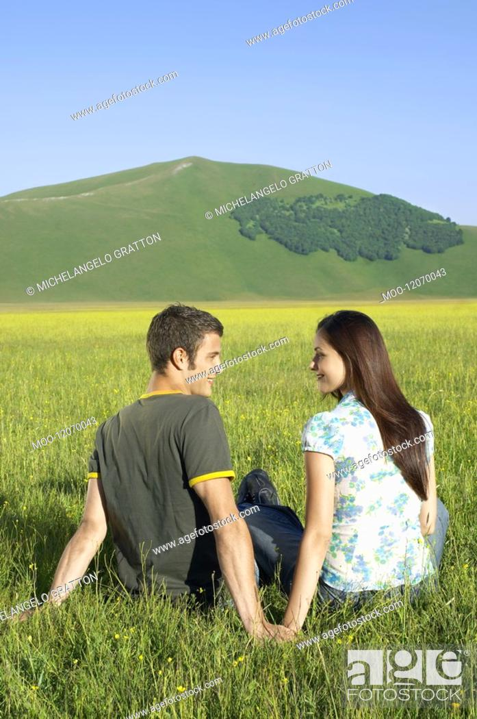 Stock Photo: Young couple sitting in mountain field back view.