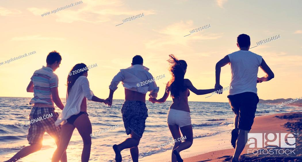 Stock Photo: happy young people group have fun white running and jumping on beacz at sunset time.