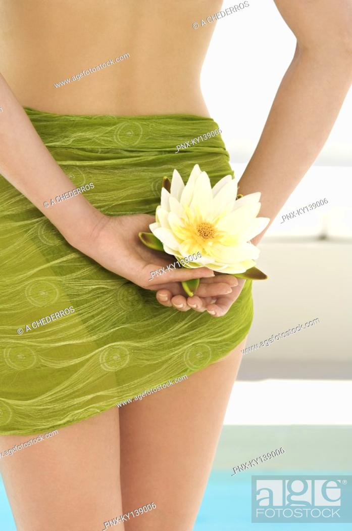 Stock Photo: Young woman holding a water lily, pool, outdoors.
