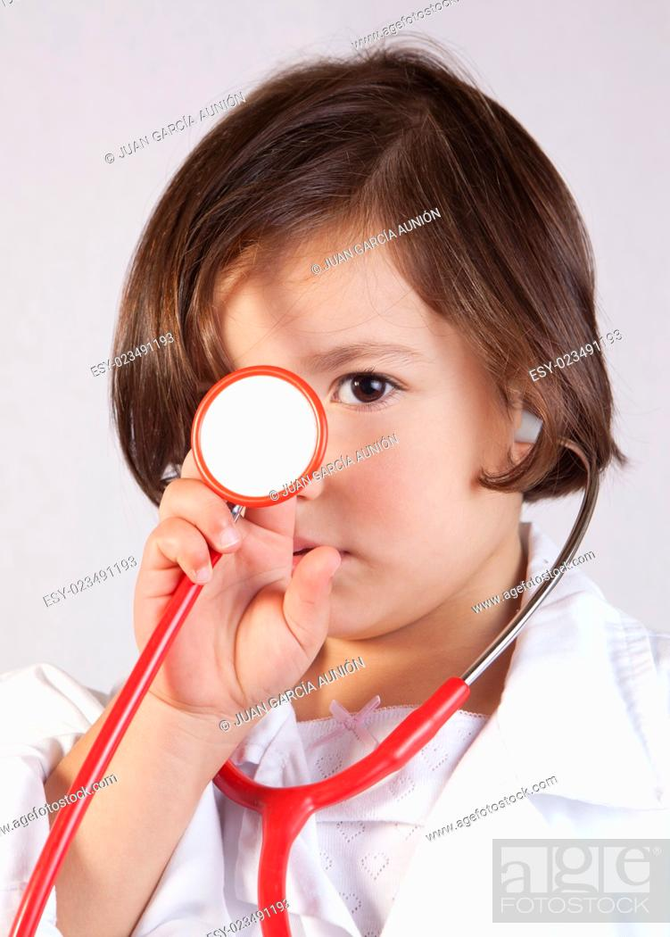 Stock Photo: Little girl showing and playing with a stethoscope. Isolated over white background.