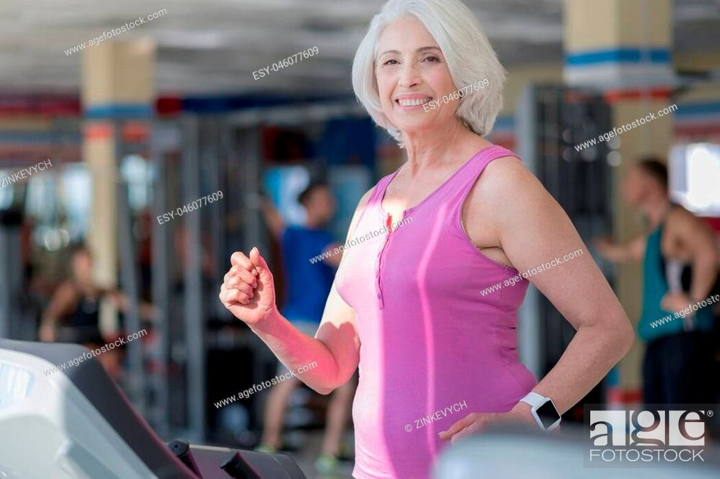 Stock Photo: Happy running. Emotional pretty senior woman smiling and running on treadmill while training in a gym.