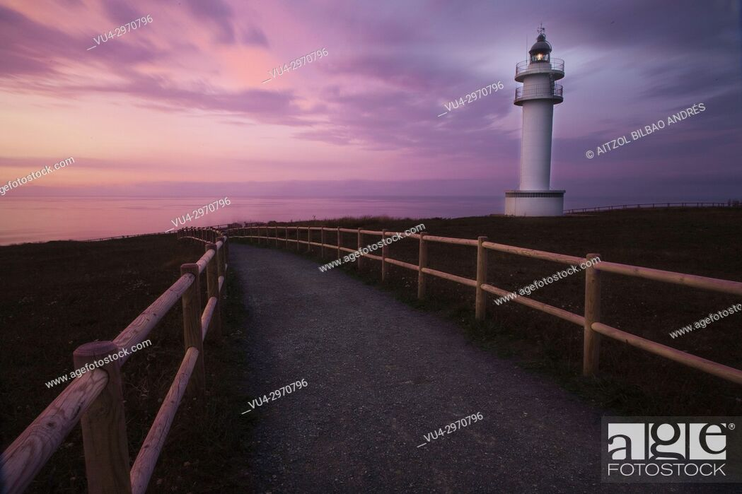 Stock Photo: Sunset at Ajo lighthouse, cantabria, spain. The small road creates a nice effect.