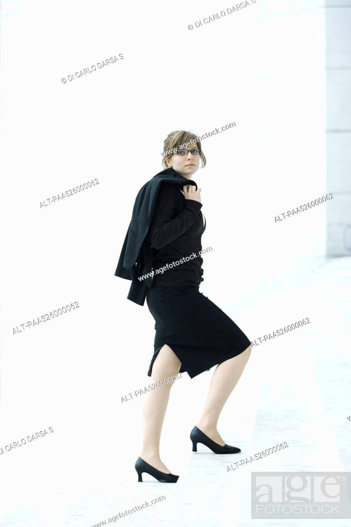 Stock Photo: Businesswoman, jacket on shoulder walking up steps.