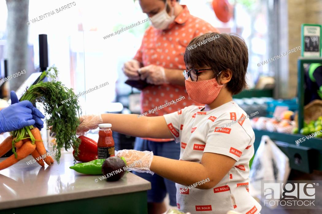 Stock Photo: Young boy with mask at counter of supermarket.