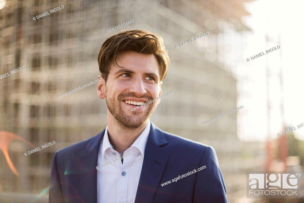 Stock Photo: Portrait of smiling businessman in front of construction site looking sideways.