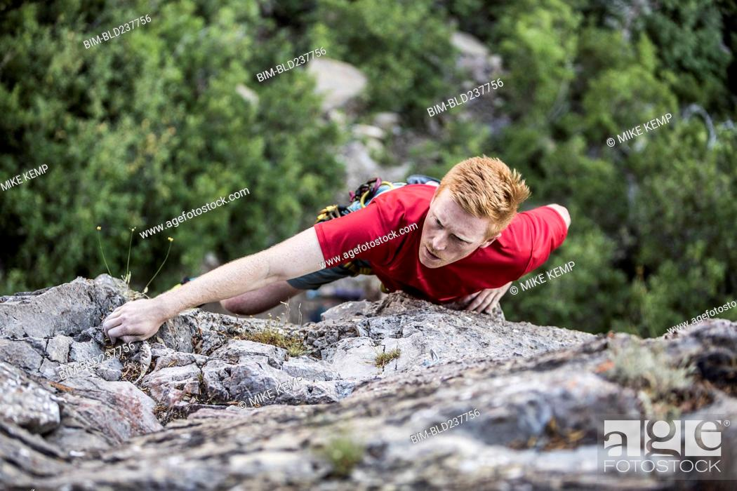 Stock Photo: Caucasian man rock climbing.