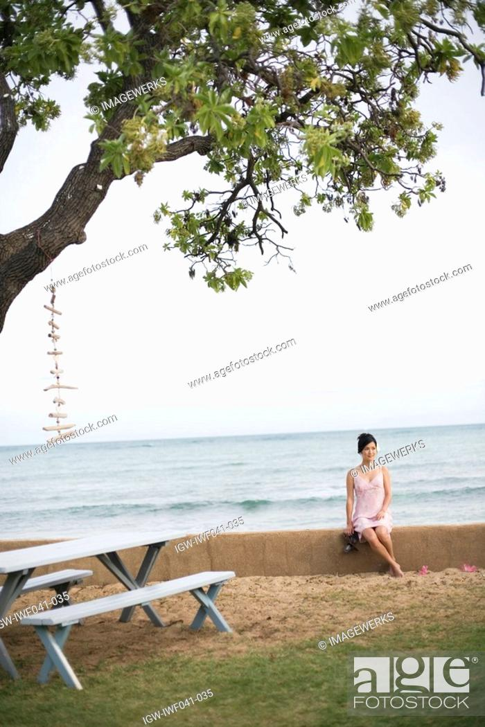 Stock Photo: View of a woman sitting on wall by sea.