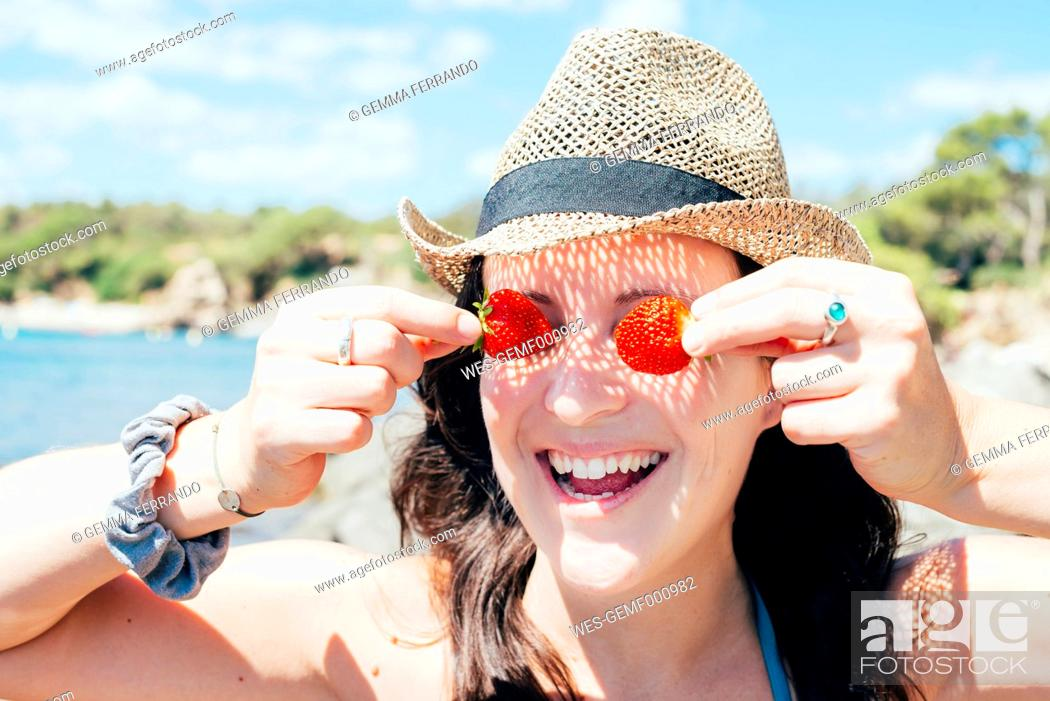 Stock Photo: Portrait of smiling woman wearing straw hat on the beach covering her eyes with strawberries.