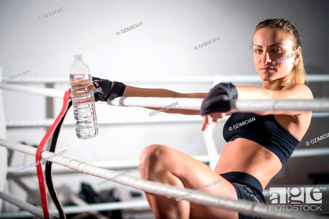 Young adult sexy boxing girl drinking water after training