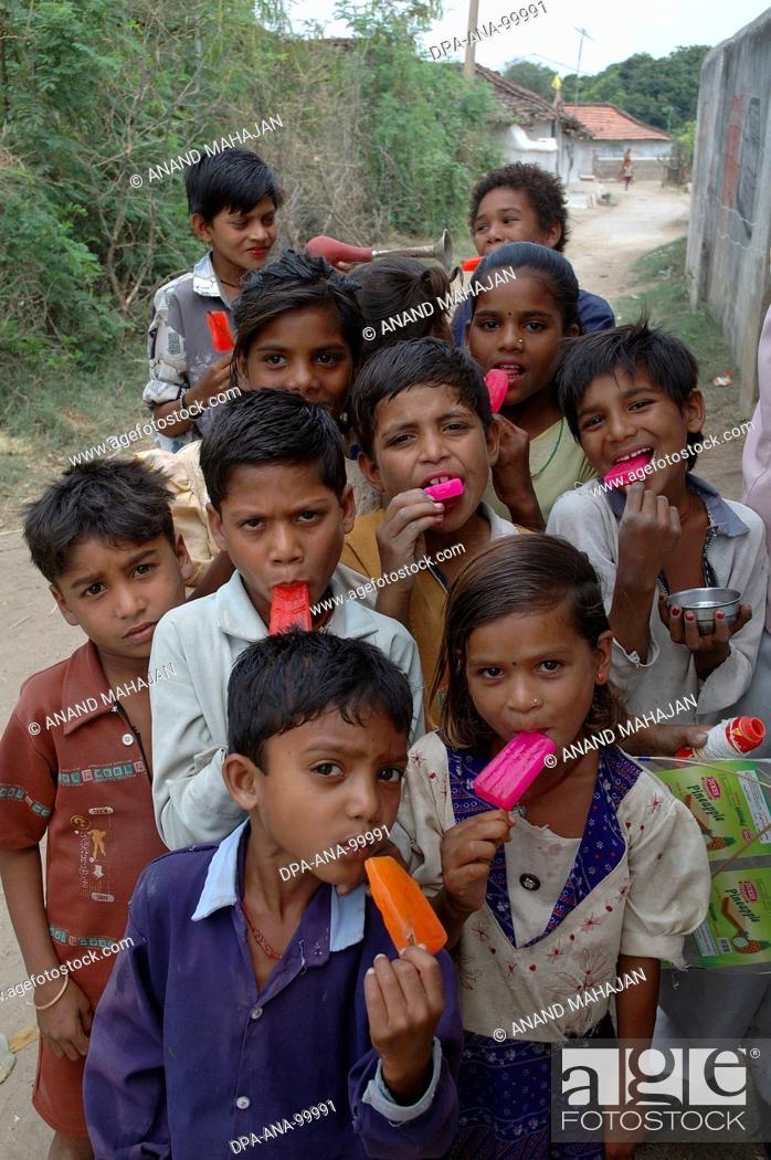 Stock Photo: School going children eating red color ice cream , Village Manghawa , District Narsinghpur , Madhya Pradesh , India.