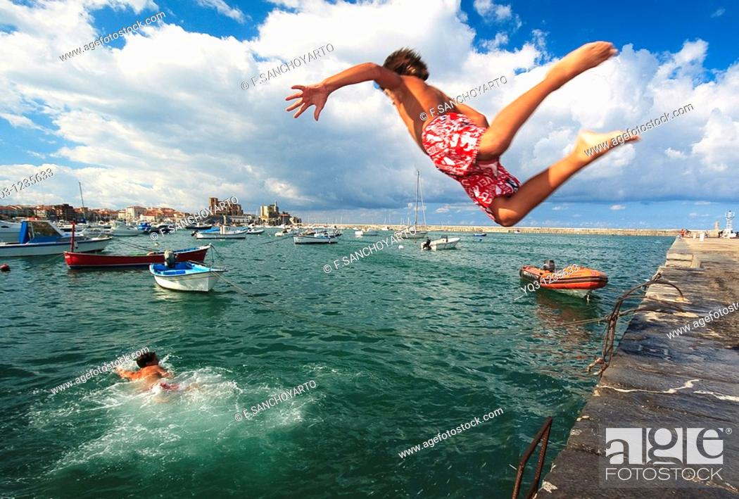 Stock Photo: Children jumping in water at Muelle Don Luis. Castro Urdiales Bay, Cantabria, Spain.