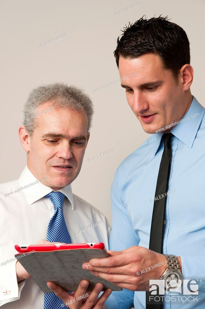 Stock Photo: Business colleagues, one young and one older, discuss work using tablet computer.
