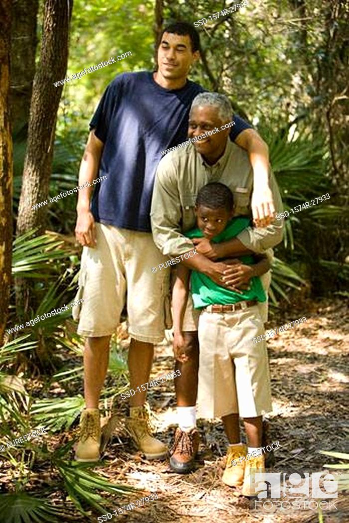 Stock Photo: Mature man with his son and friend smiling at forest.