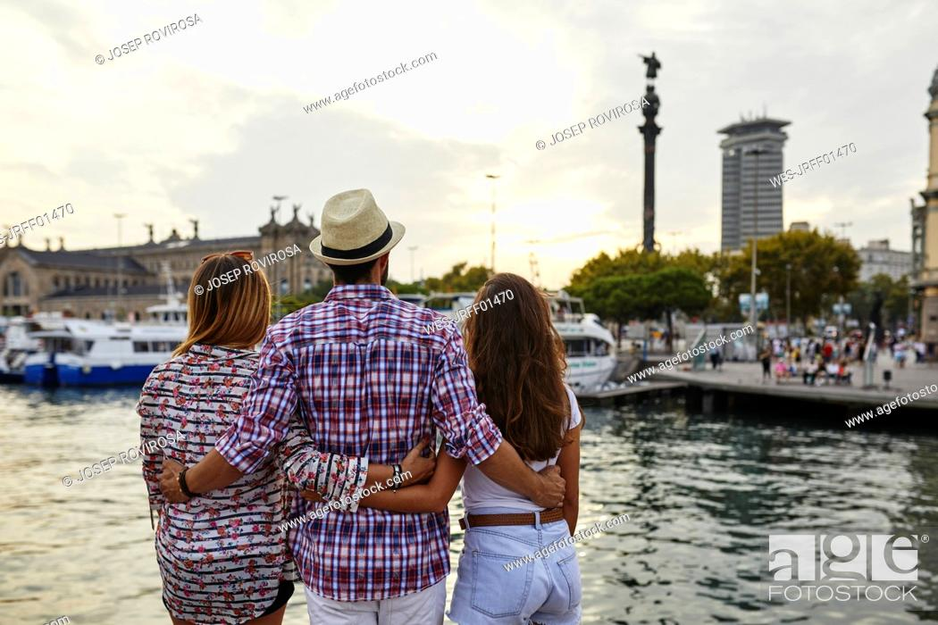 Imagen: Spain, Barcelona, three tourists embracing at the waterfront in the city.