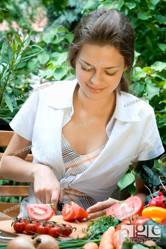 Stock Photo: Young woman cutting up tomatoes.
