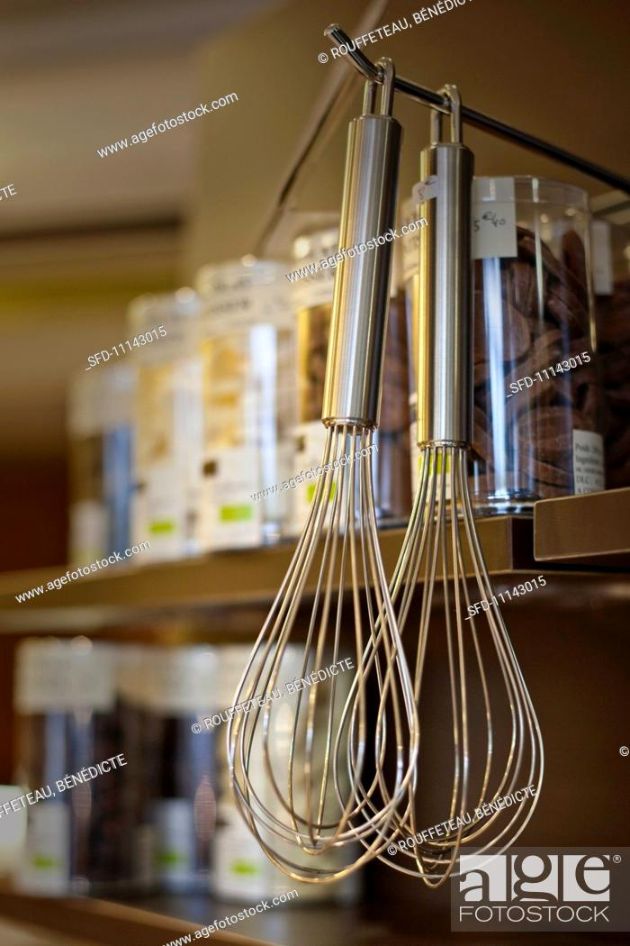 Stock Photo: Whisks hanging from a hook.
