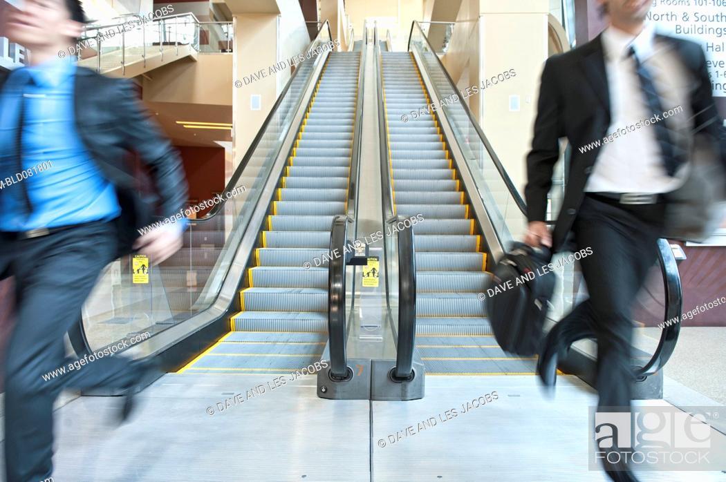 Stock Photo: Rushing businessmen running off escalator.
