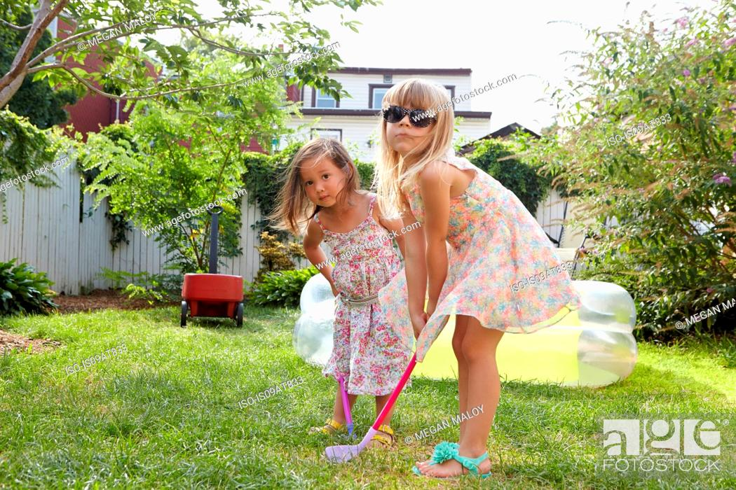Stock Photo: Girls playing kids golf in garden.