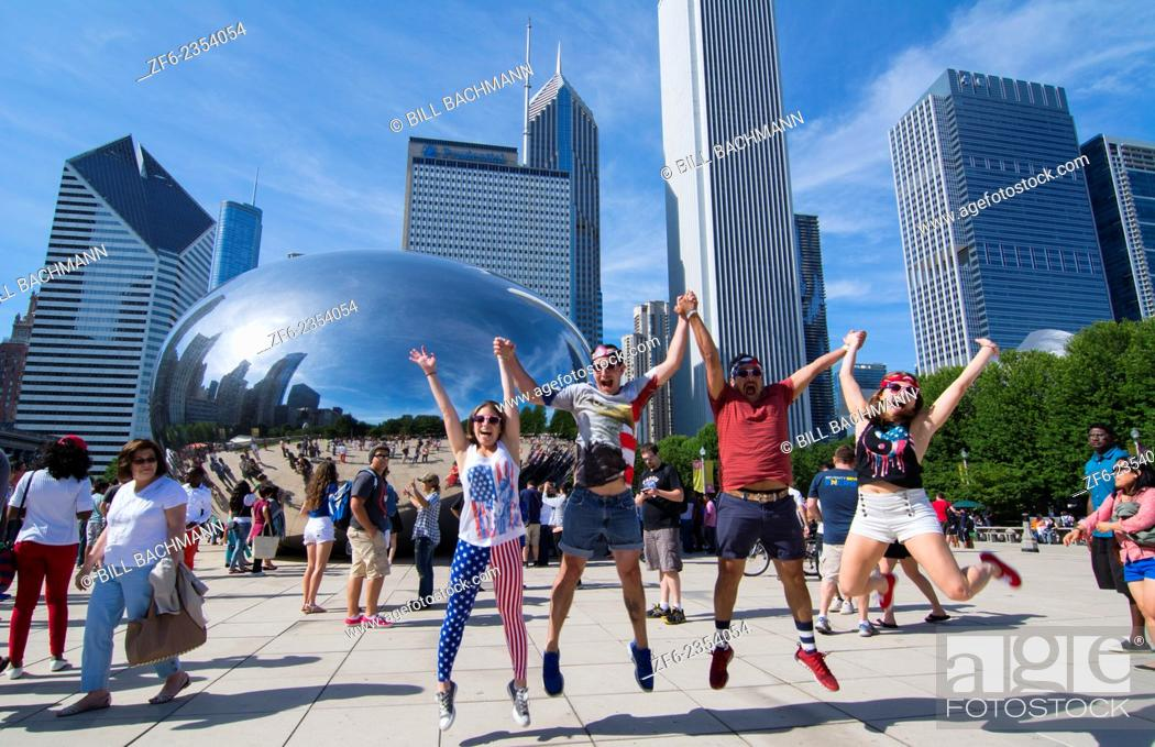 Stock Photo: Chicago Illinois Millennium Park July 4th locals jumping for joy at Cloud Gate sculpture called The Bean with skyline in background skyscrapers in downtown.