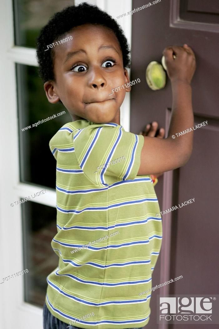 Stock Photo: A boy with a surprised expression standing at the front door or his house.