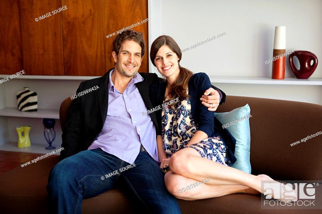 Stock Photo: Couple sitting on sofa, portrait.