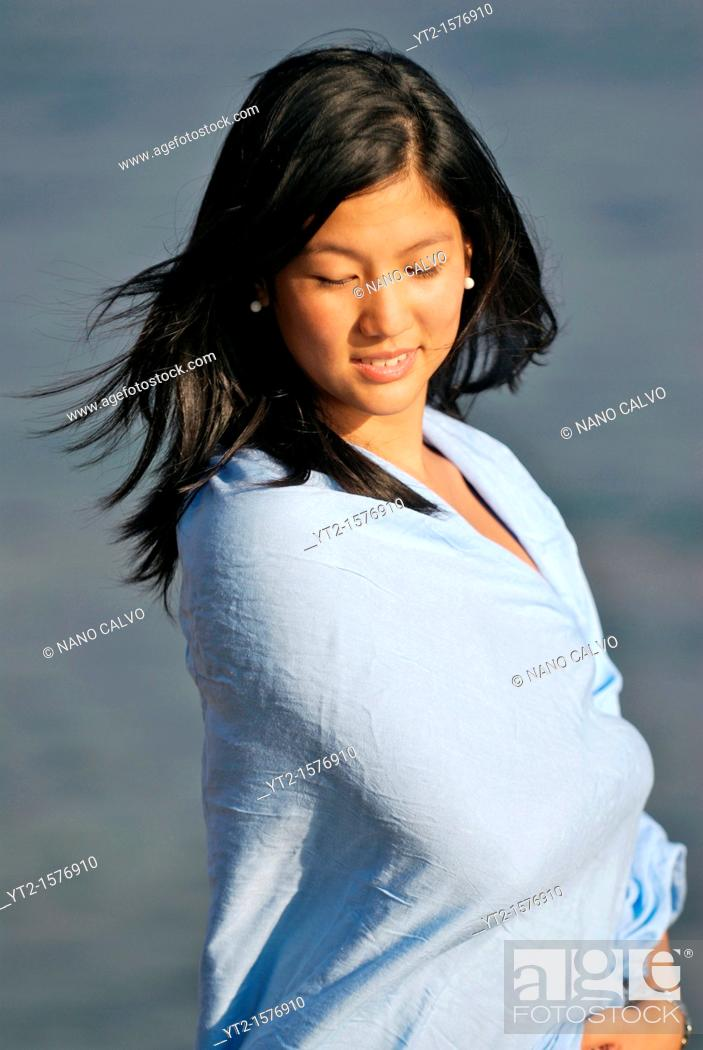 Stock Photo: Cute young asian woman on the beach.