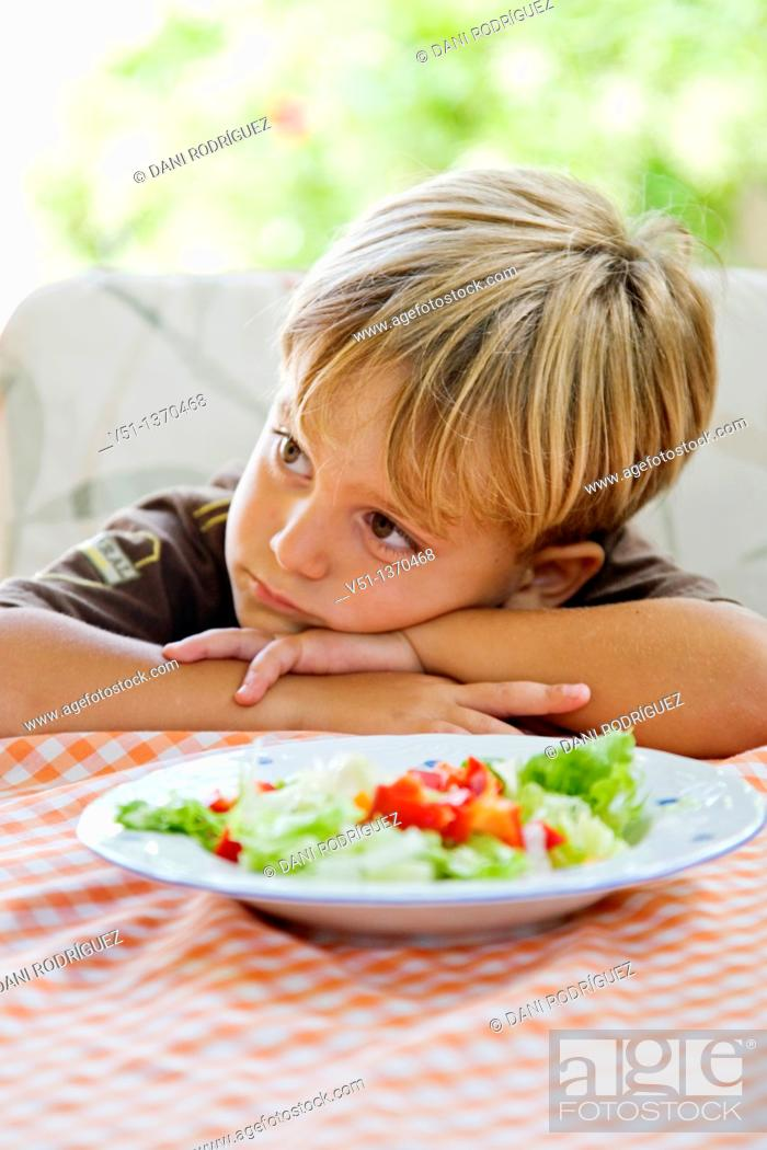 Stock Photo: Portrait of a boring boy with a plate of salad.