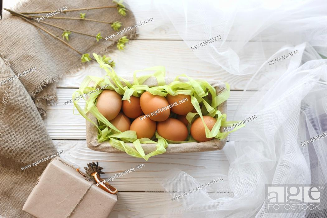 Stock Photo: Basket with eggs and spring decor on a white wooden background.