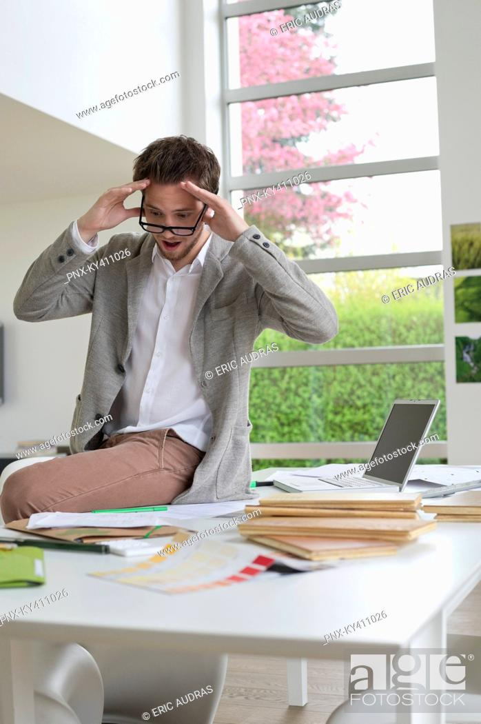 Stock Photo: Interior designer looking surprised in the office.