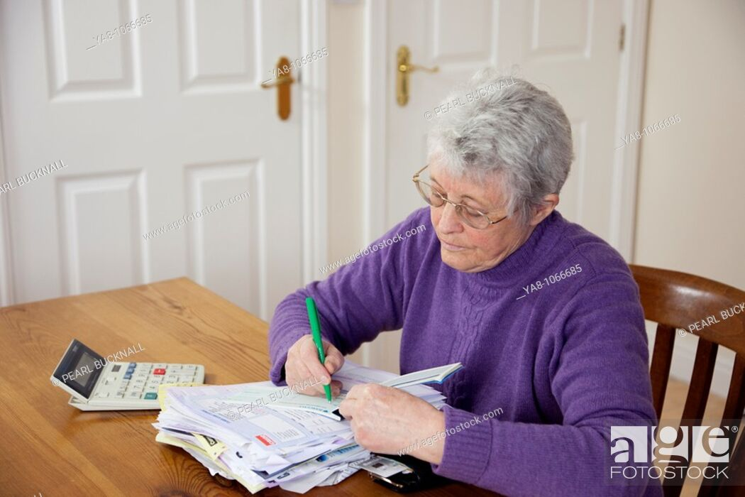 Stock Photo: Britain, UK, Europe  Senior woman pensioner with a big pile of bills on the table writing a cheque to pay.