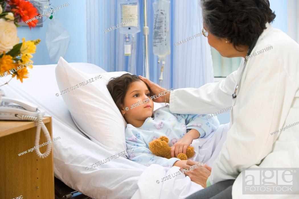 Stock Photo: Senior female doctor checking on girl in hospital bed.