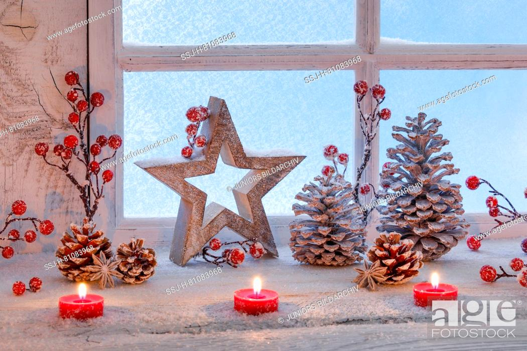 Stock Photo: Christmas decoration: Three burning red tealights, stars, berries and cones in a window. Switzerland.