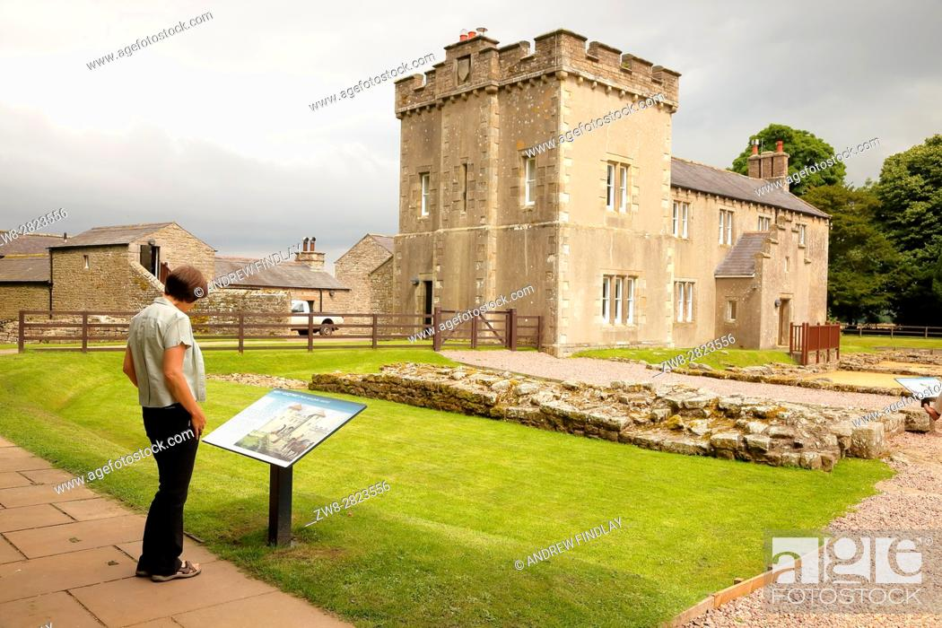 Stock Photo: Woman reading information sign. Banna, Birdoswald Roman Fort, Cumbria, England, United Kingdom, Europe.